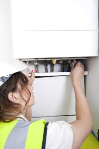 Plumber-Working-200x300 Female plumber servicing central heating boiler